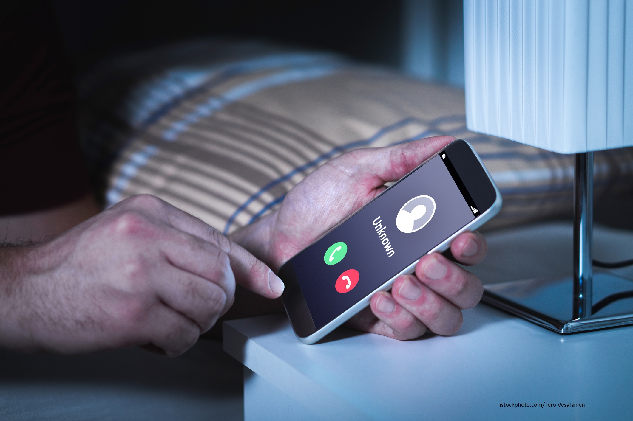 Unknown number calling in the middle of the night. Phone call from stranger. Person holding mobile and smartphone in bedroom bed home late.