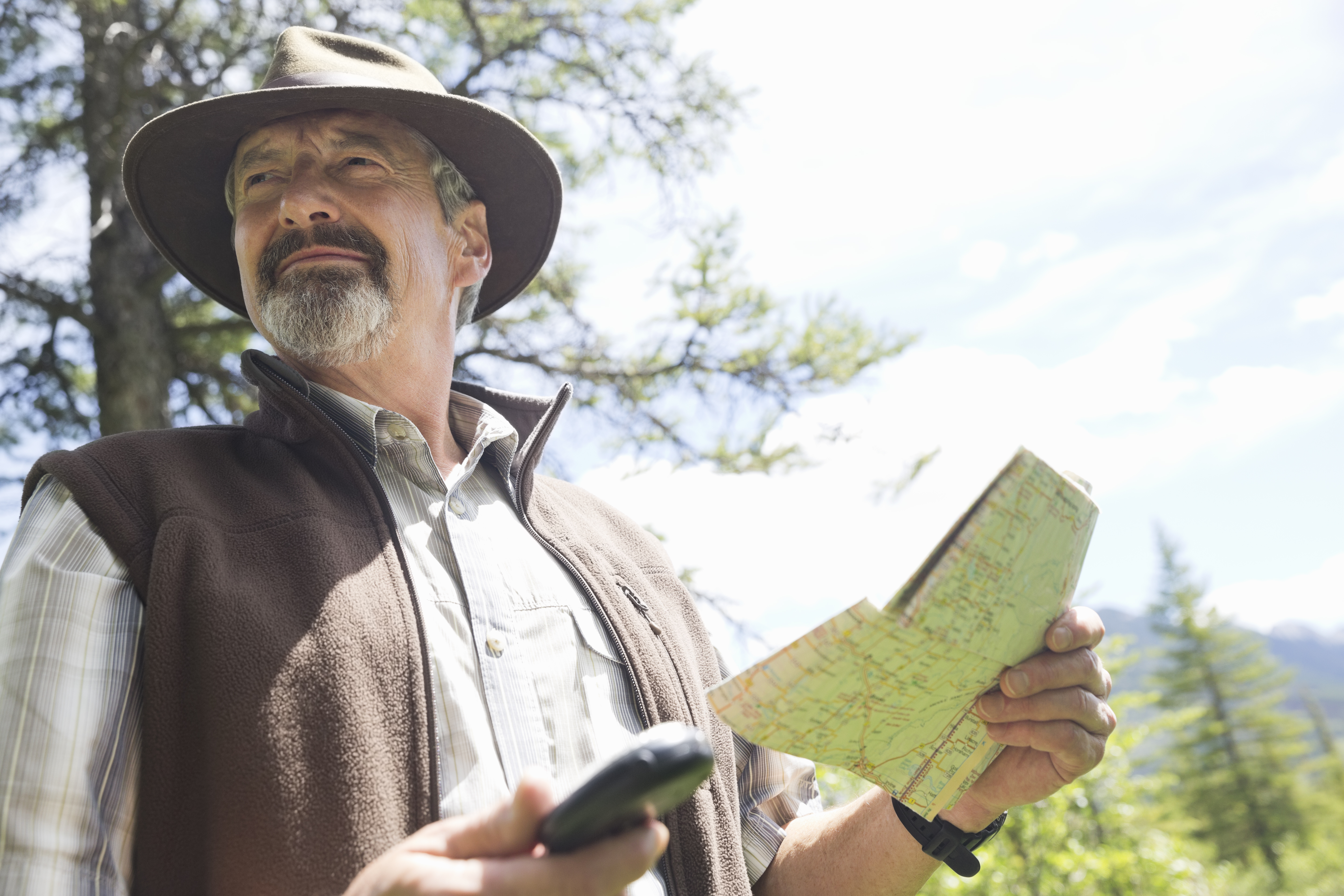 Senior man holding map and compass in forest