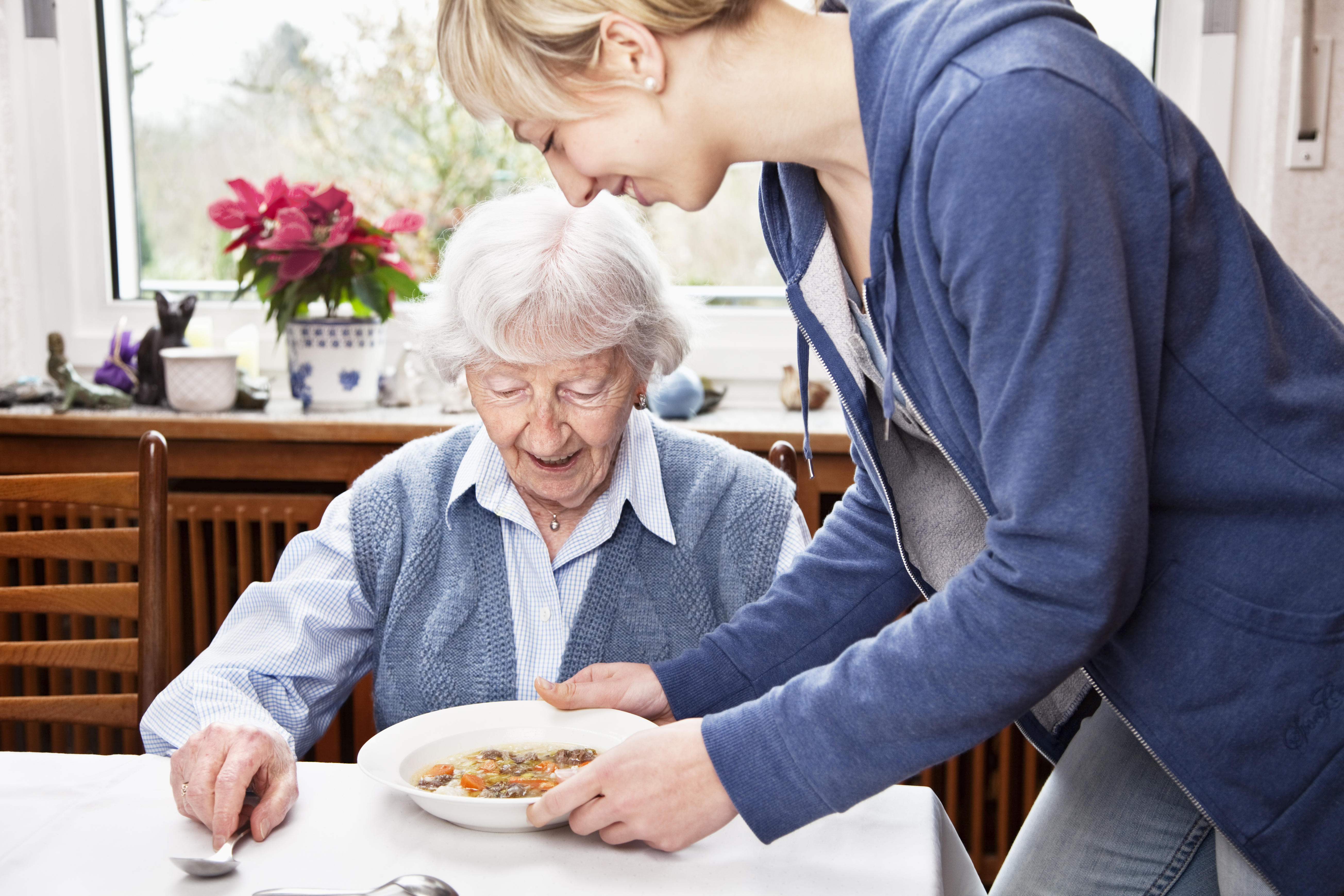 senior woman getting soup served by caregiver