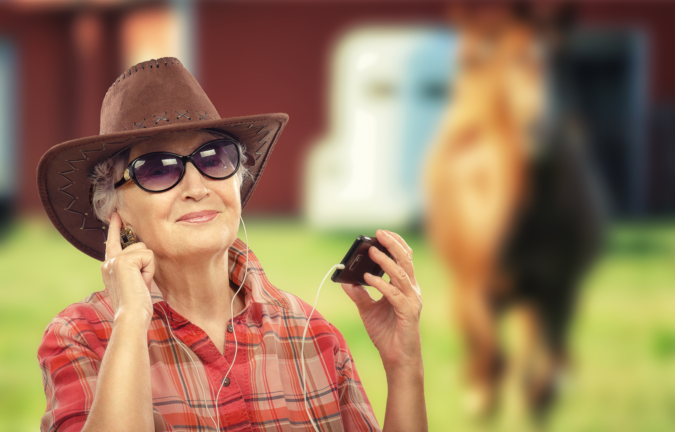 Aged cowgirl listening music with smart phone