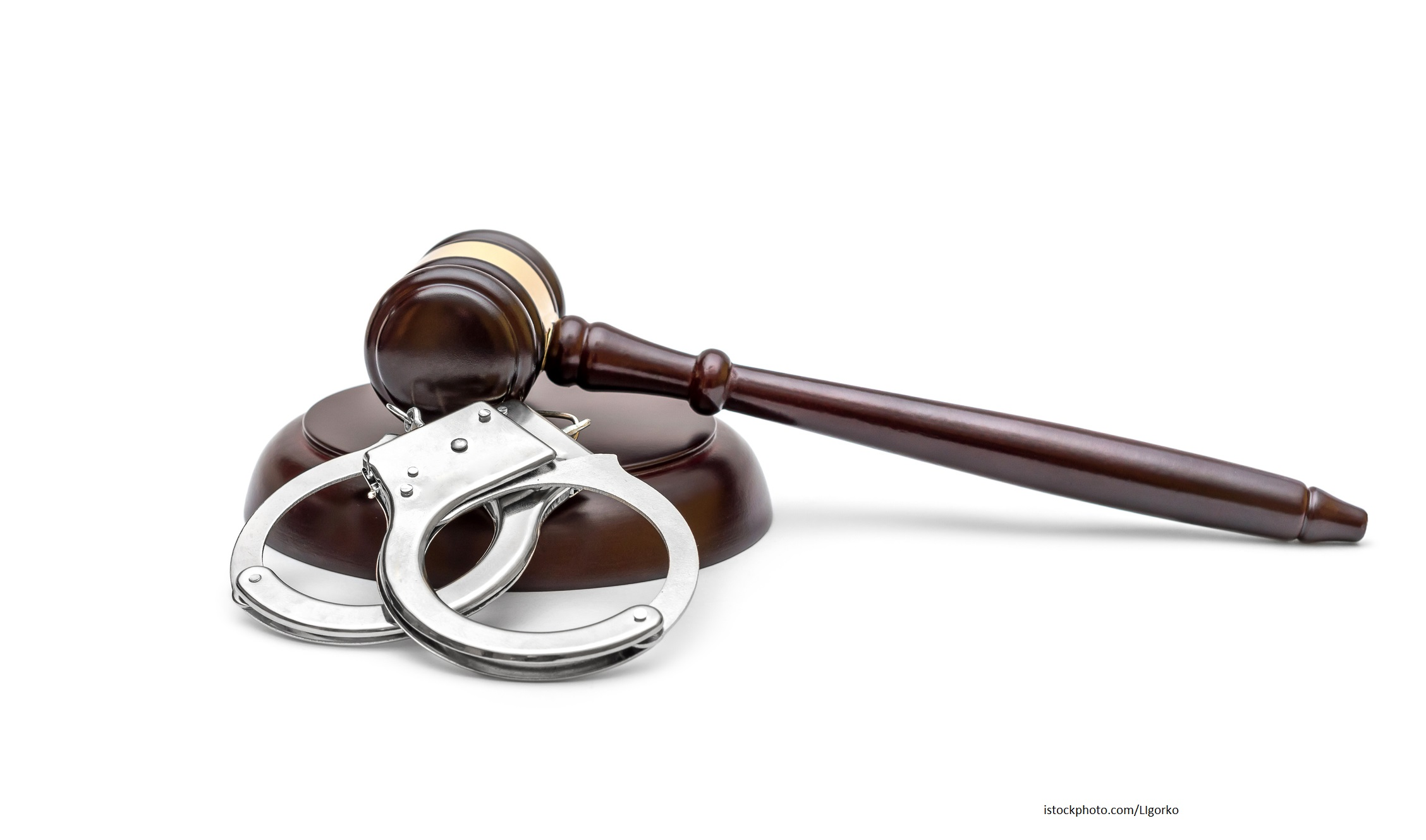 Handcuffs with judge's gavel on white background. Law concept.