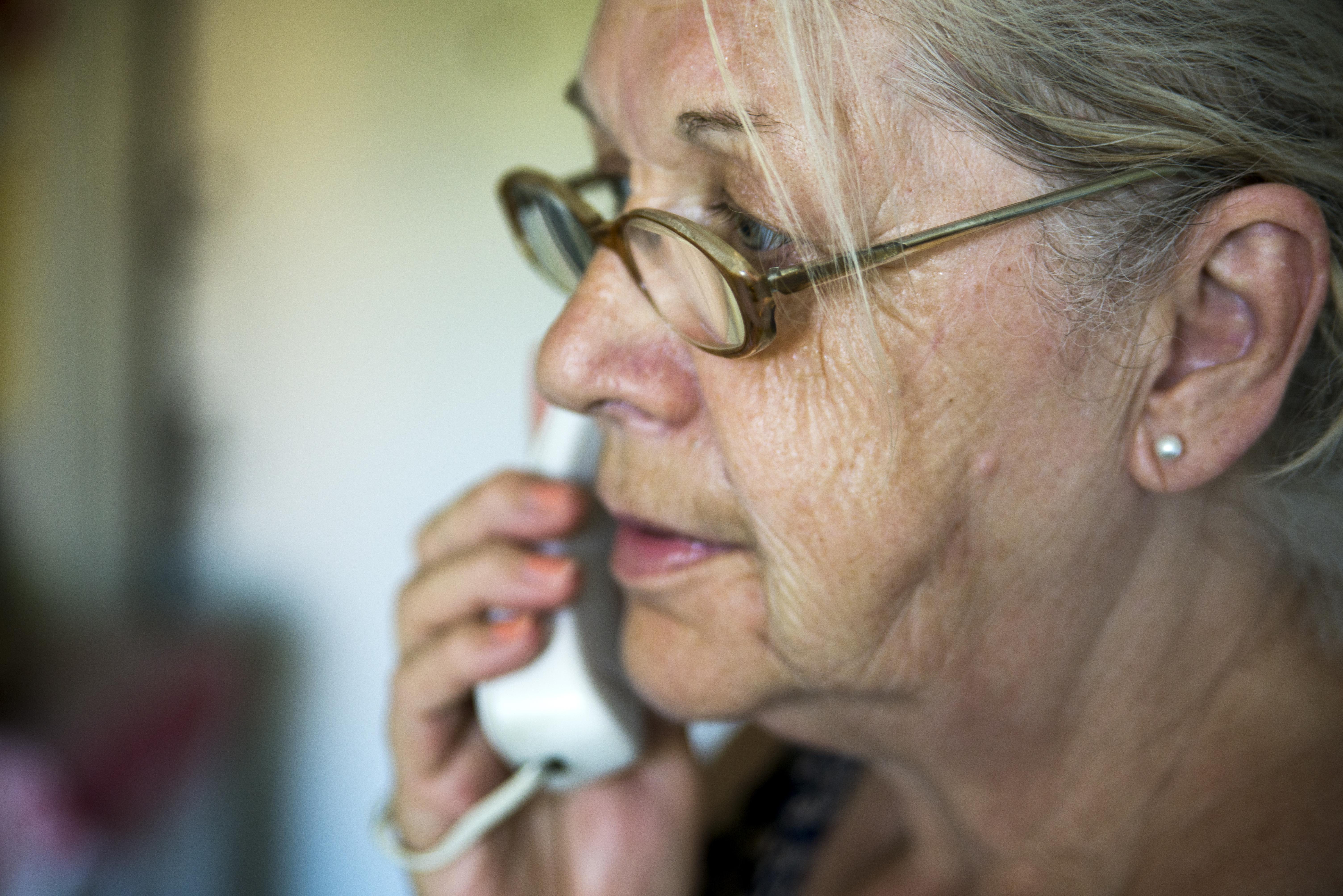 worried mature woman talking on telephone