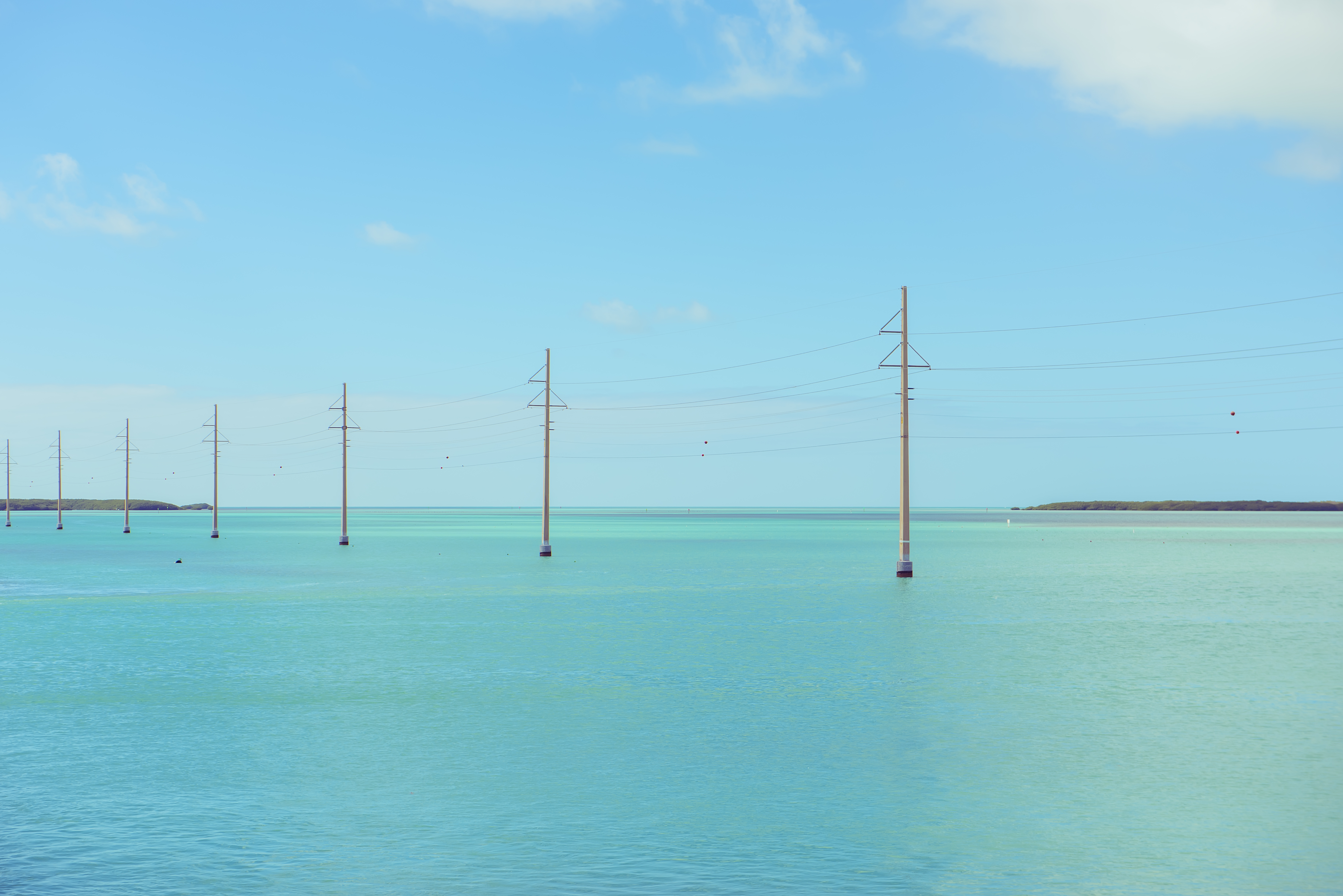Electric posts in the emerald bay water. Beautiful view of the ocean bay. Florida. USA