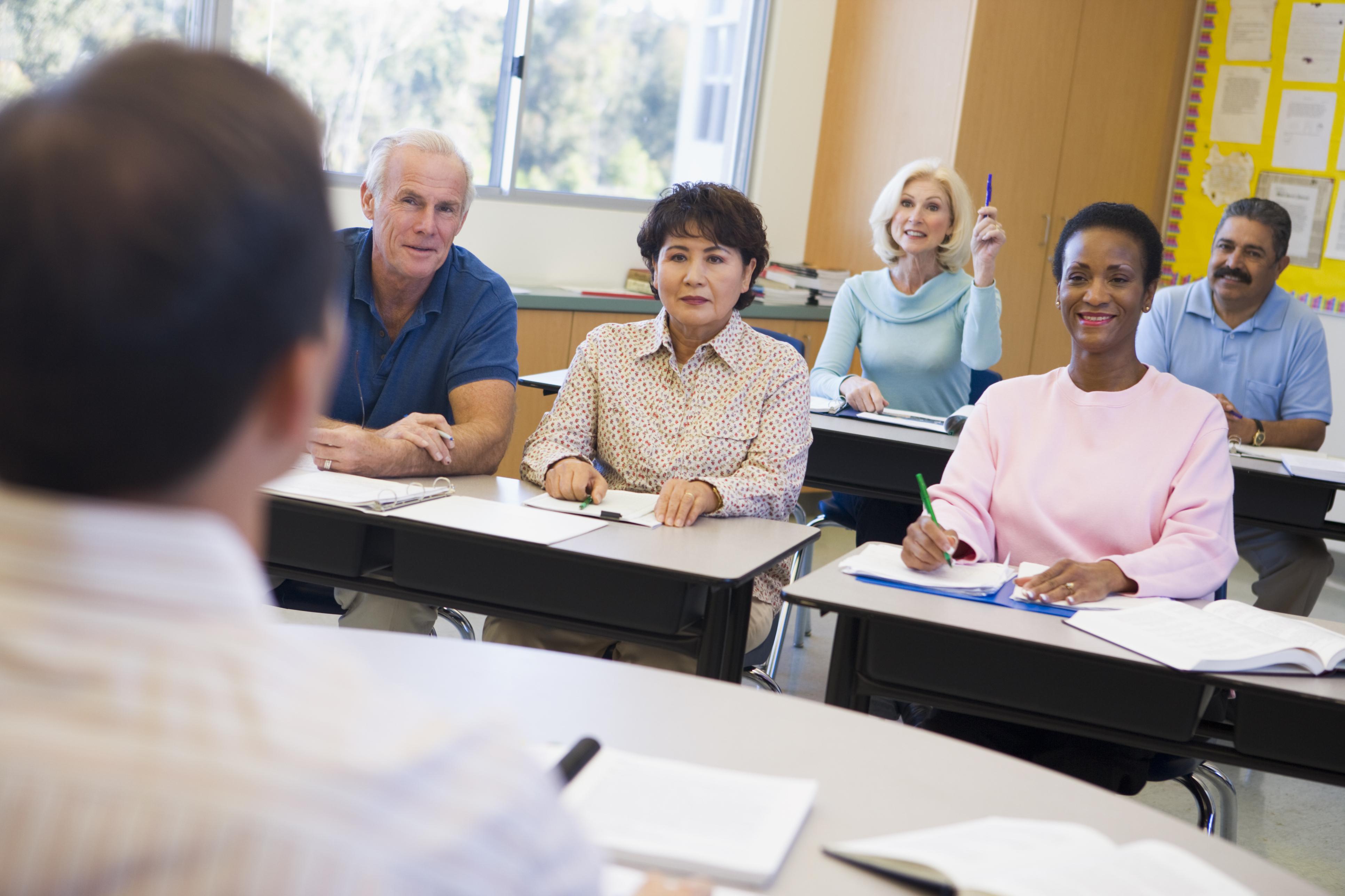 Mature female student raising hand in class