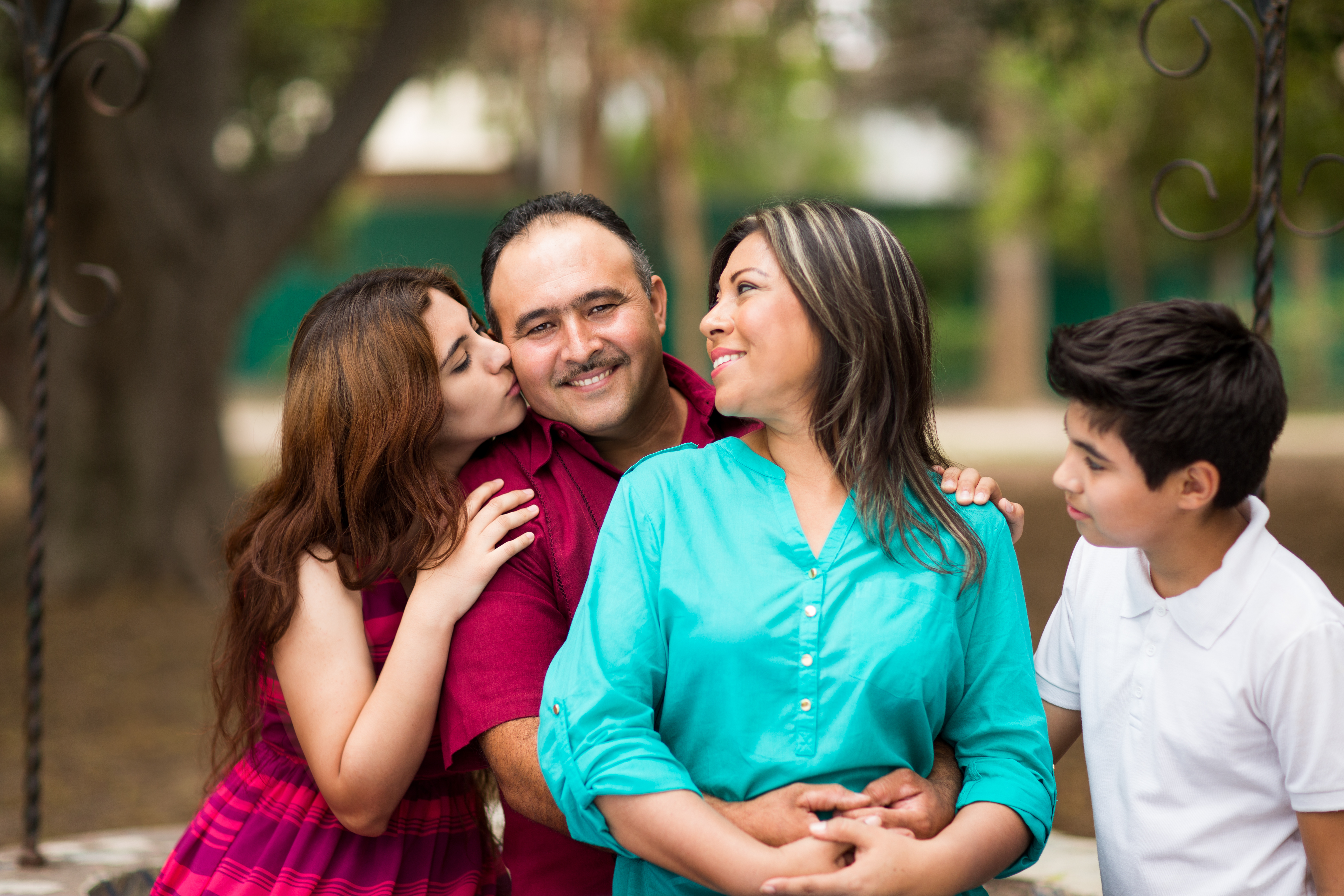 Latin family of four showing affection