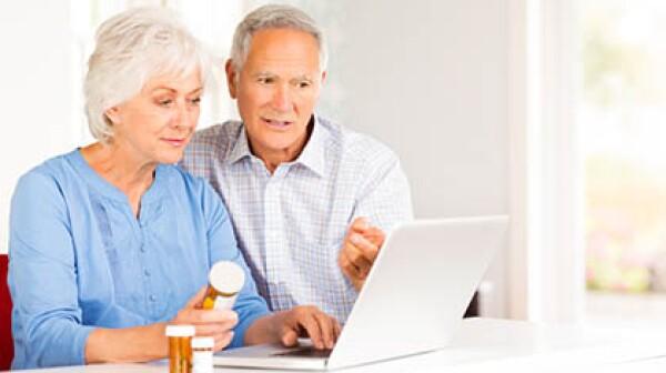 Senior Couple With Pill Bottles Browsing Internet On Laptop.